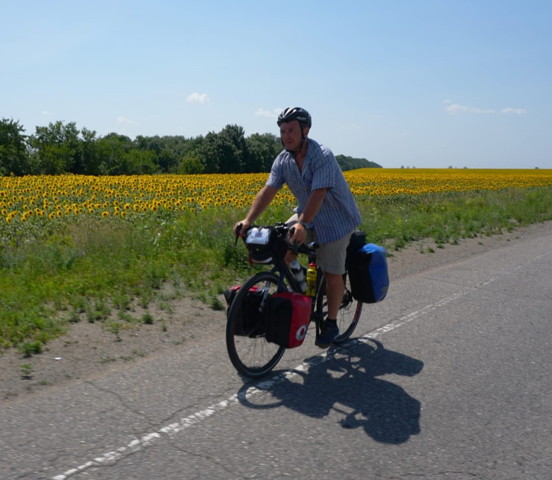 Keith riding the Ukraine farmfields with Sunflowers